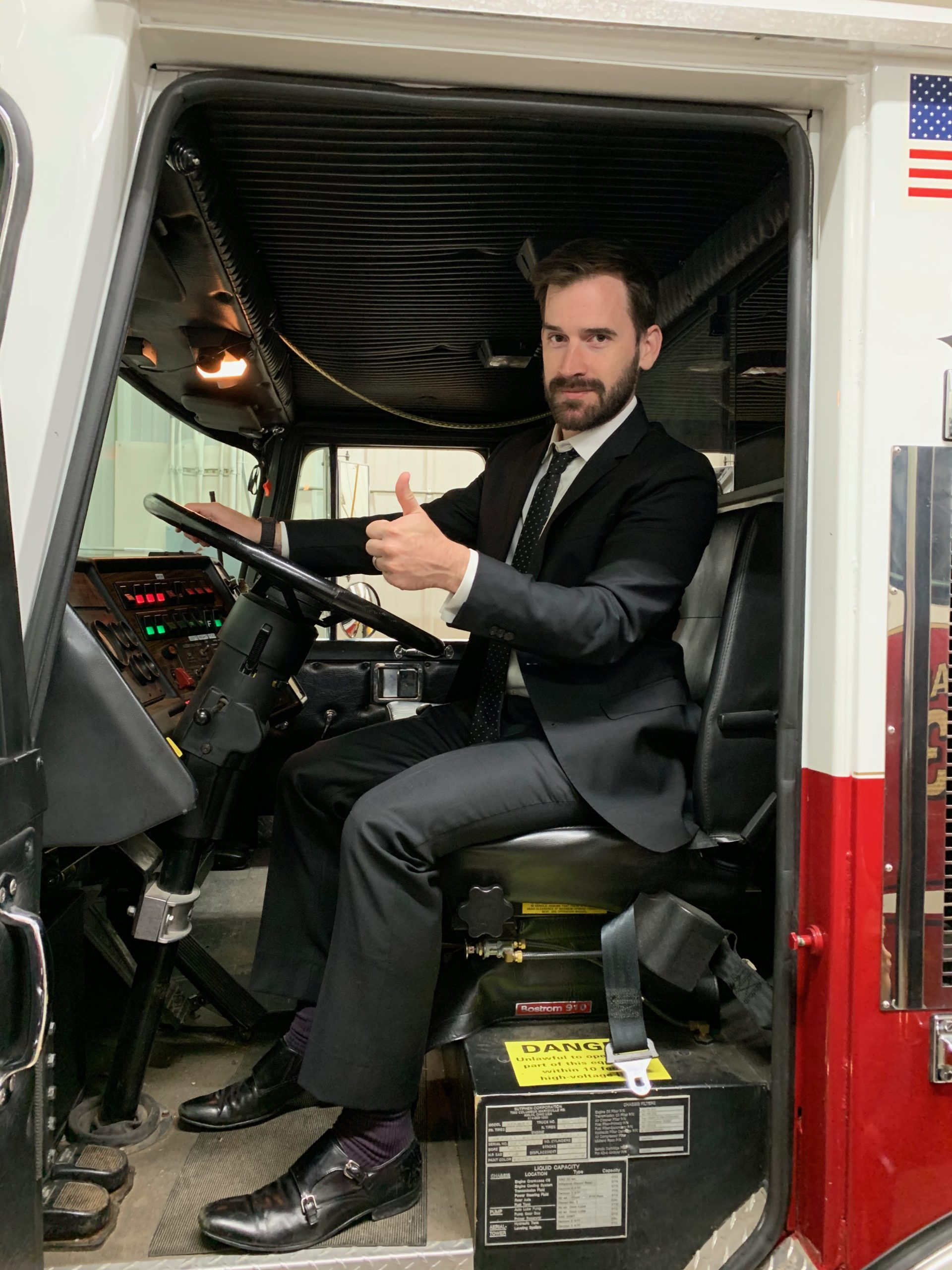 Dan Winckler sitting behind the wheel of a firetruck wearing a black suit and giving a thumbs-up.